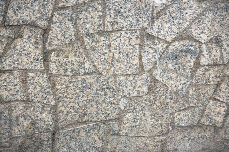 Decoratieve die het onder ogen zien of stoepoppervlakte, als asymmetrisch mozaïek van grijze granitstukken wordt gemaakt verschil stock afbeelding