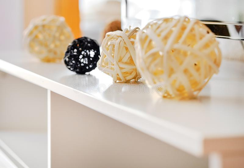 Decoratieve gele en zwarte verschillende vormenballen, rijs van natuurlijke materialen op een witte lijst binnen van woonkamer, t stock foto's