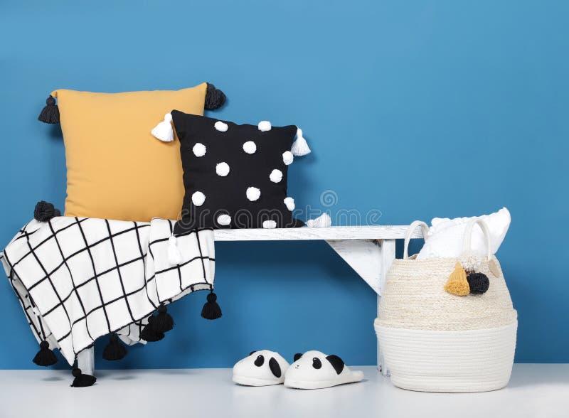 Decoratieve hoofdkussens en deken met pom-poms op een houten bank, comfortabele zachte pantoffels en een rieten mand royalty-vrije stock afbeeldingen