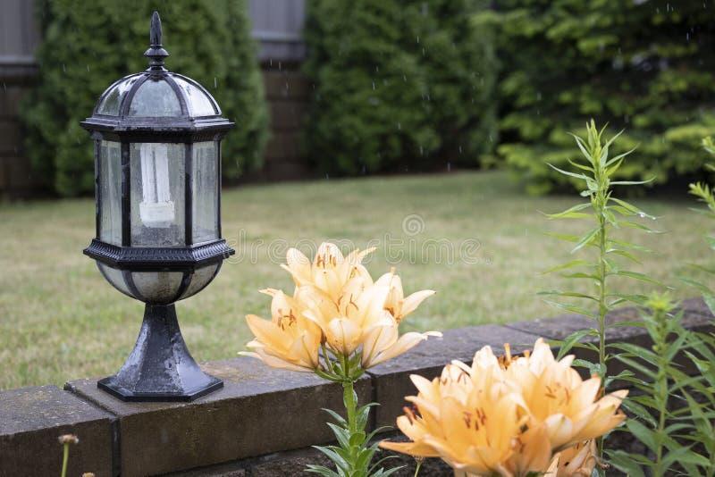 Decoratieve lantaarn in de tuin dichtbij een bloembed met oranje lelies stock afbeelding