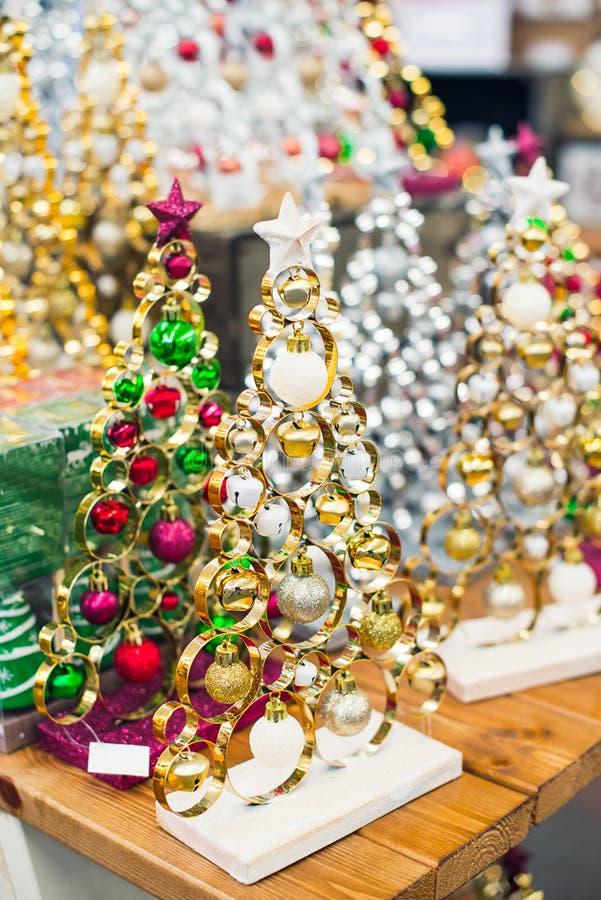 Decoratieve metaal zilveren en gouden moderne kanten Kerstmisbomen met rode en groene ballen op houten lijst aangaande lichte bok stock afbeeldingen