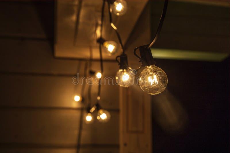 Decoratieve openluchtkoordlichten die op boom in de tuin bij nacht hangen stock afbeelding