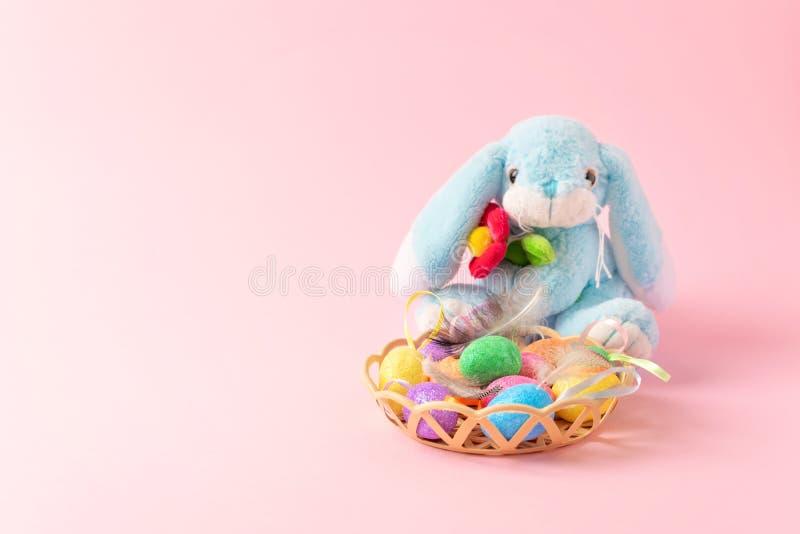 Decoratieve paaseieren met veren bij mand en zacht stuk speelgoed konijn op roze achtergrond Pasen-samenstelling, groetkaart met stock fotografie