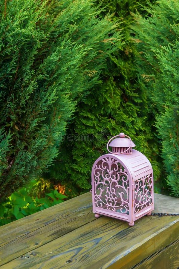 Decoratieve roze glaslamp met kaarsen, tribunes op een houten bank in de tuin royalty-vrije stock afbeeldingen