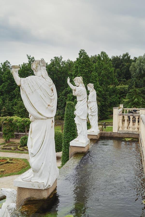 Decoratieve vijver met aan de kant de rug van drie Roman statuten stock fotografie