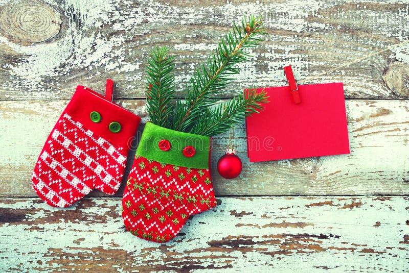 Decoratieve vuisthandschoenen, sparrentak en lege rode kaart op een kabel tegen de achtergrond van de oude verwijderde raad stock afbeeldingen