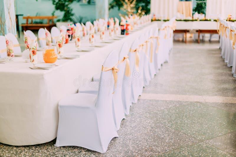 Decoratieve Witte Mantels en Gekleurde Linten op Stoelen bij Feestelijke Lijst stock afbeeldingen