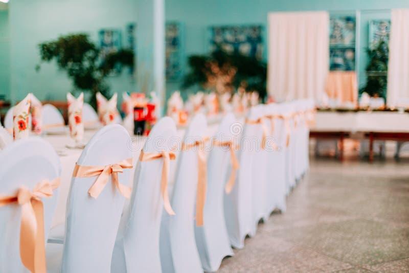 Decoratieve Witte Mantels en Gekleurde Linten op Stoelen bij Feestelijke Lijst stock afbeelding