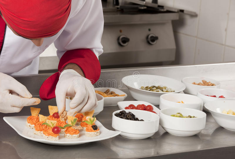 Decorating canapes with tomato stock photography