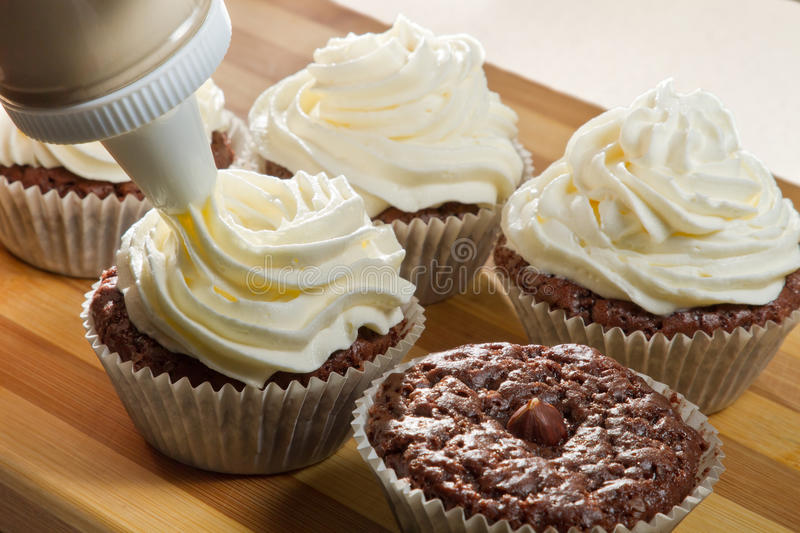 Decorating chocolate muffin with vanilla cream royalty free stock images