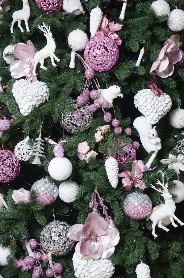 Decorating Christmas tree close up. Decoration bulb, fir tree, pink x-mas toys and lights. Use for Christmas and New years. Celebration background royalty free stock images