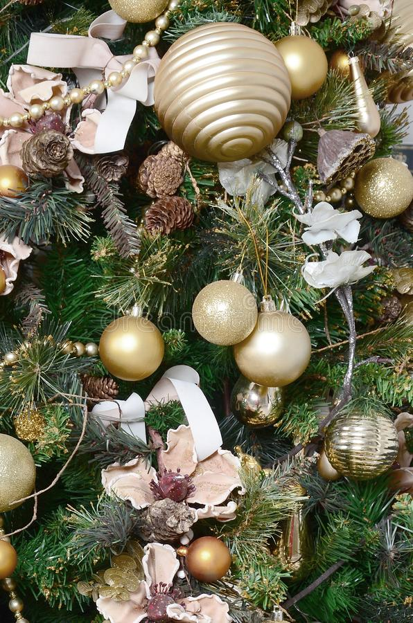 Decorating Christmas tree close up. Decoration bulb, green fir tree, golden x-mas toys and lights. Use for Christmas and New years. Celebration background royalty free stock photos