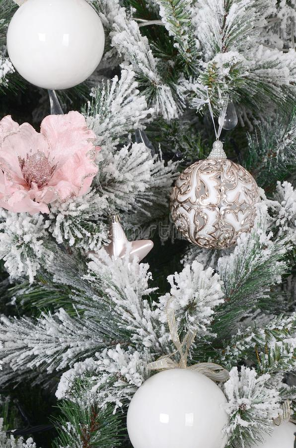 Decorating Christmas tree close up. Decoration bulb, snowy green fir tree, pink x-mas toys and lights. Use for Christmas and New. Years celebration background royalty free stock images