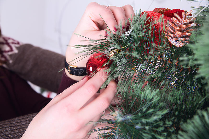Decorating christmas tree at home. hand holding red ball royalty free stock images