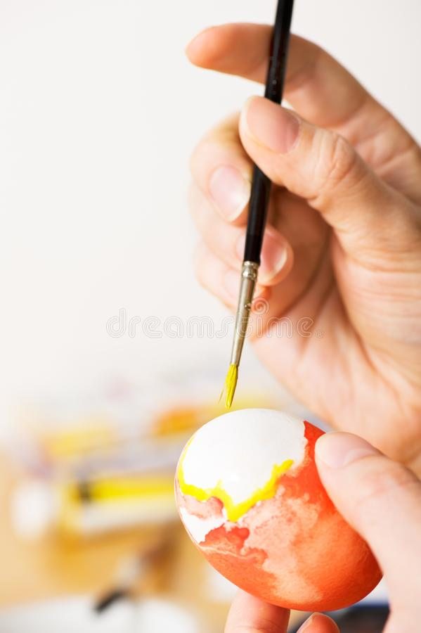 Decorating easter egg with watercolors stock images