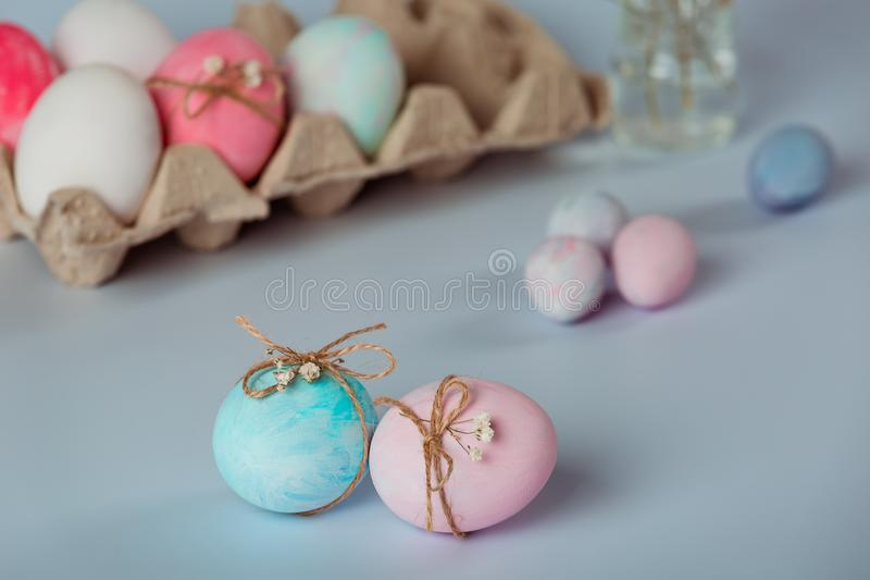 Decorating eggs. Easter is coming soon. Easter decor. Blue and pink egg is decorated with a thread. Tray with white and pink eggs on a gray background. Easter stock photo