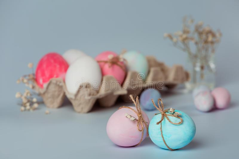 Decorating eggs. Easter is coming soon. Easter decor. Blue and pink egg is decorated with a thread. Tray with white and pink eggs on a gray background. Easter royalty free stock photo