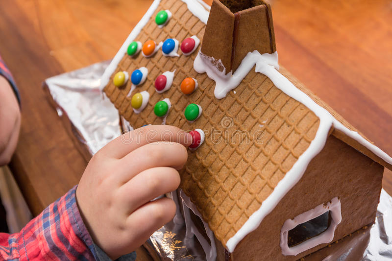 Decorating a gingerbread house royalty free stock image