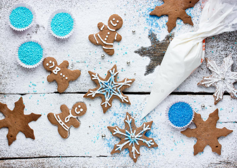 Decorating gingerbread man and snowflake Christmas cookie background, Christmas treats for kids cooking process royalty free stock photo