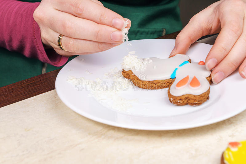 Decorating gingerbread. In the shape of a rabbit with coconut stock photo