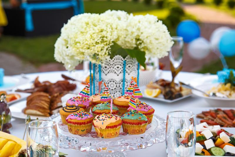 Decorating the festive table in blue with cupcakes stock images