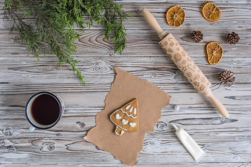 Decorating honey gingerbread cookies in a form of christmas tree on wooden grey table and craft paper. Blank biscuit gingerbread. Small fir, ready to decorate royalty free stock image