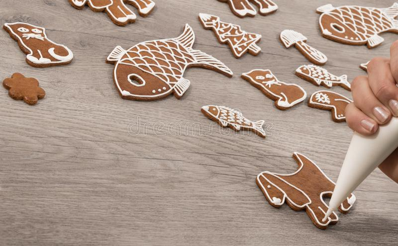 Decorating a sweet gingerbread in shape of dog royalty free stock photo