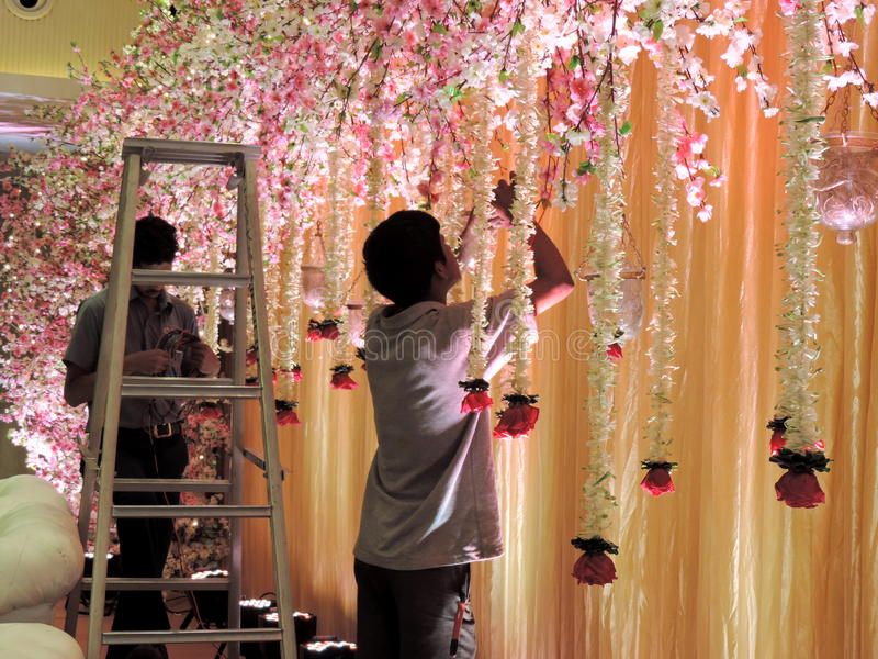 Decorating wedding reception hall at traditional Hindu wedding, India. Men decorating the wedding reception hall with flowers for a Hindu wedding in India. The royalty free stock photography