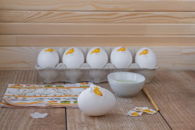 Decorating white eggs for Easter using decoupage technique. Sticking a piece of paper napkin with the image of a cute chicken using raw protein. Wood royalty free stock images