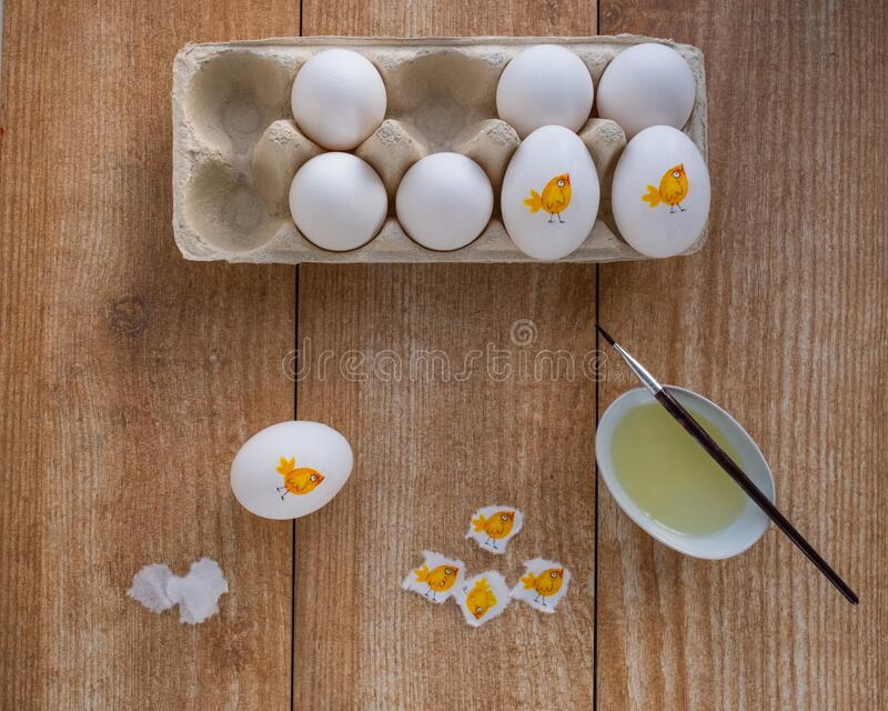Decorating white eggs for Easter using decoupage technique. Sticking a piece of paper napkin with the image of a cute chicken using raw protein. Flat lay Top royalty free stock photography