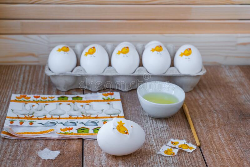 Decorating white eggs for Easter using decoupage technique. Sticking a piece of paper napkin with the image of a cute chicken using raw protein. Wood royalty free stock photos
