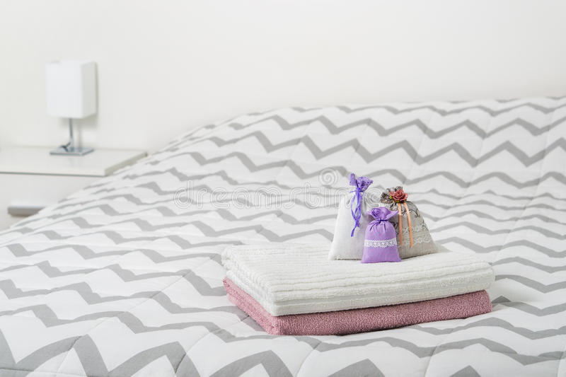 Decoration accessories and light color Scandinavian interior design. Scented sachets and lavender pouches on towels on bed. stock photo