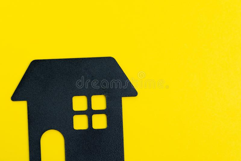 Decoration black house shape on solid yellow background with copy space using as happy home, good living and lifestyle or buy and stock photo
