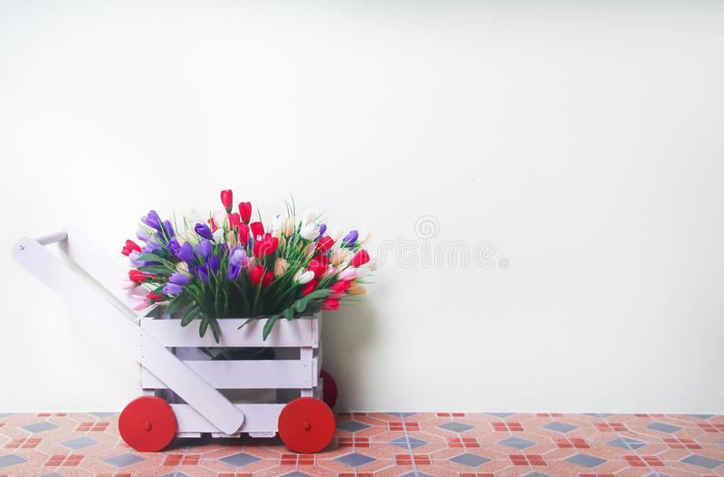 Decoration  colorful flowers in wood pot hand freight patterns shaped on white wall background stock photos