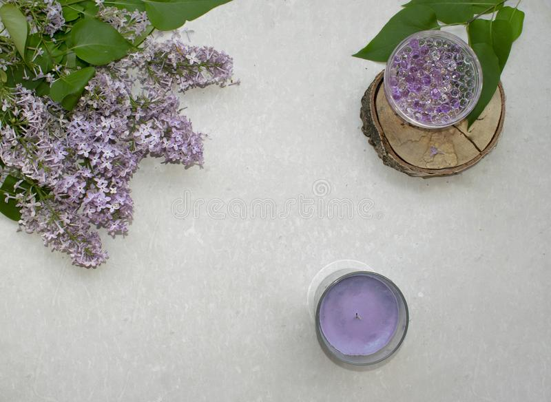 Decoration flat lay with a bouquet flowers lilac. Spa lavender candle and hydrogel balls on wooden slice on grey background stock images