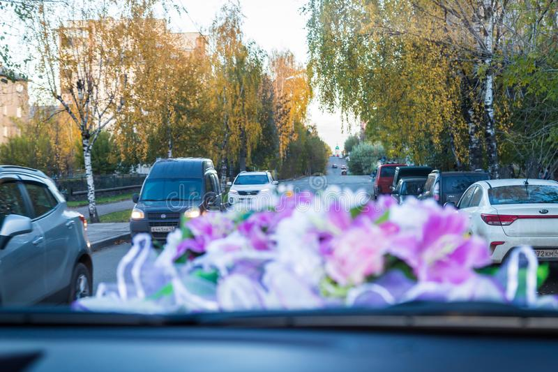Decoration flowers on the roof of the wedding car in Russia and the street with cars in the blur royalty free stock photo