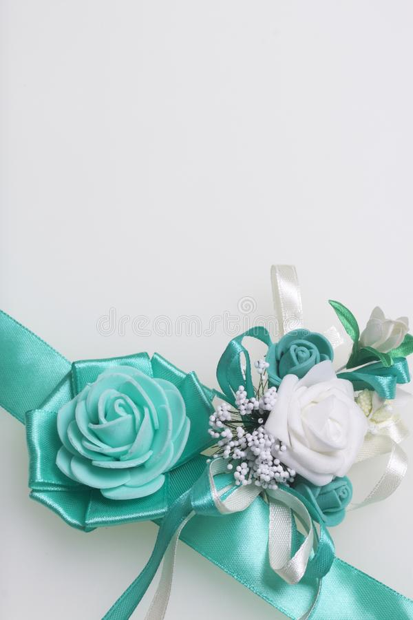 Decoration on hand in the form of a rose of emerald color, sewn to a satin ribbon. Near the wedding boutonniere. On a white backgr stock photography