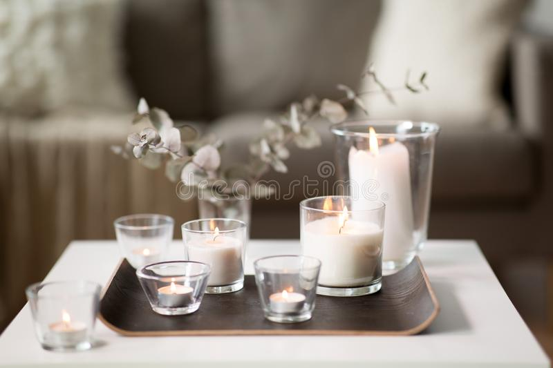 Burning fragrance candles on table at cozy home stock image