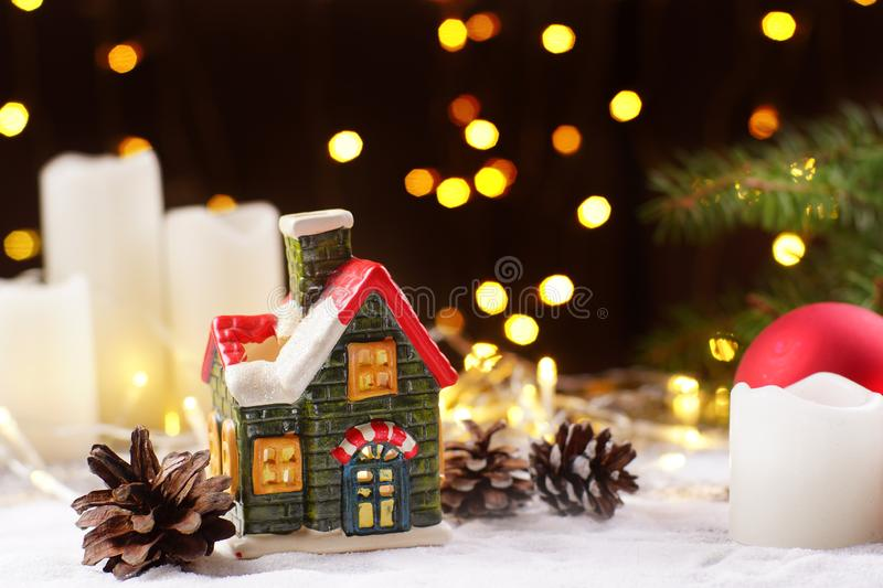 Decoration of the New Year`s table in the form of a clay house, white candles with sparkling garlands on a dark stock photography