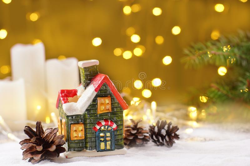 Decoration of the New Year`s table in the form of a clay house, white candles with sparkling garlands on a golden stock photography