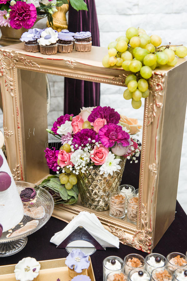 Decoration with pink, white and red flowers in golden wooden frame. Wedding decor with grapes and cookies. Fresh roses stock image