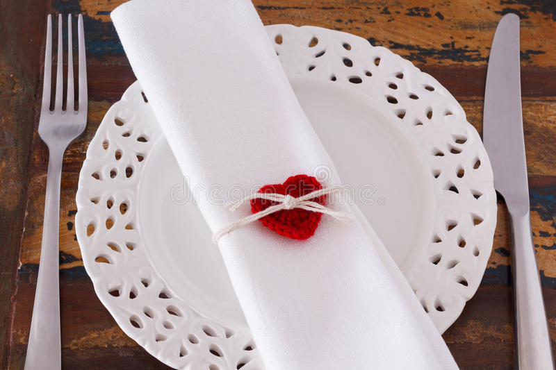 Decoration Saint Valentine's day: White plate serviette fork knife with handmade red crochet heart. Decoration for Saint Valentine's day: White plate serviette royalty free stock images