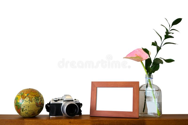 Decoration scene of blank travel photo frame, vintage camera, globe model and clear glass bottle vase with pink flower and green royalty free stock photo