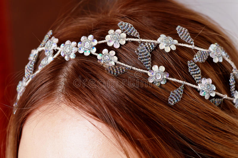 Decoration of silver beading on the girl`s hair. Close royalty free stock photo
