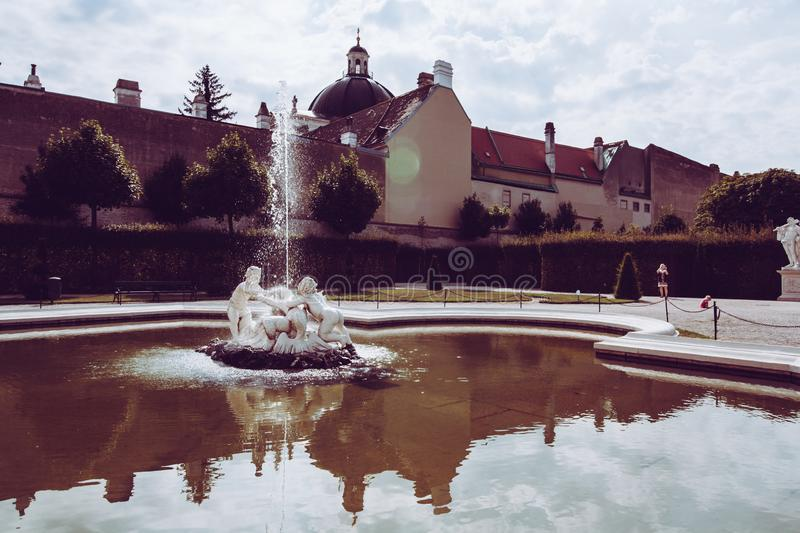 Decoration statue of a medieval fountain in the garden on the background of bright cloudy sky. Water spraying out of stature on royalty free stock photography