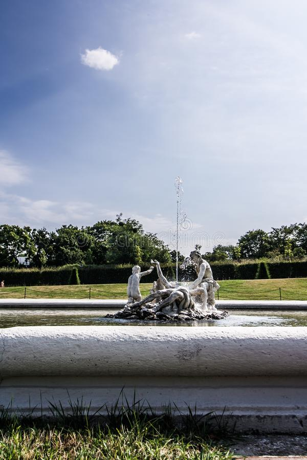 Decoration statue of a medieval fountain in the garden on the background of bright sky. Water spraying out of stature on fountain royalty free stock photos