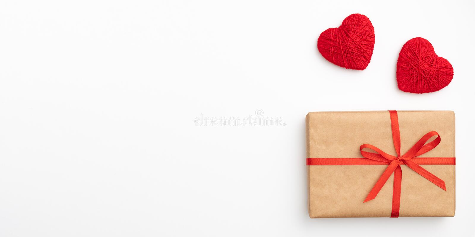 Decoration valentine`s day on table desk top view with present box. Flat lay composition of red heart and craft paper gift box. With red bow ribbon isolated royalty free stock image