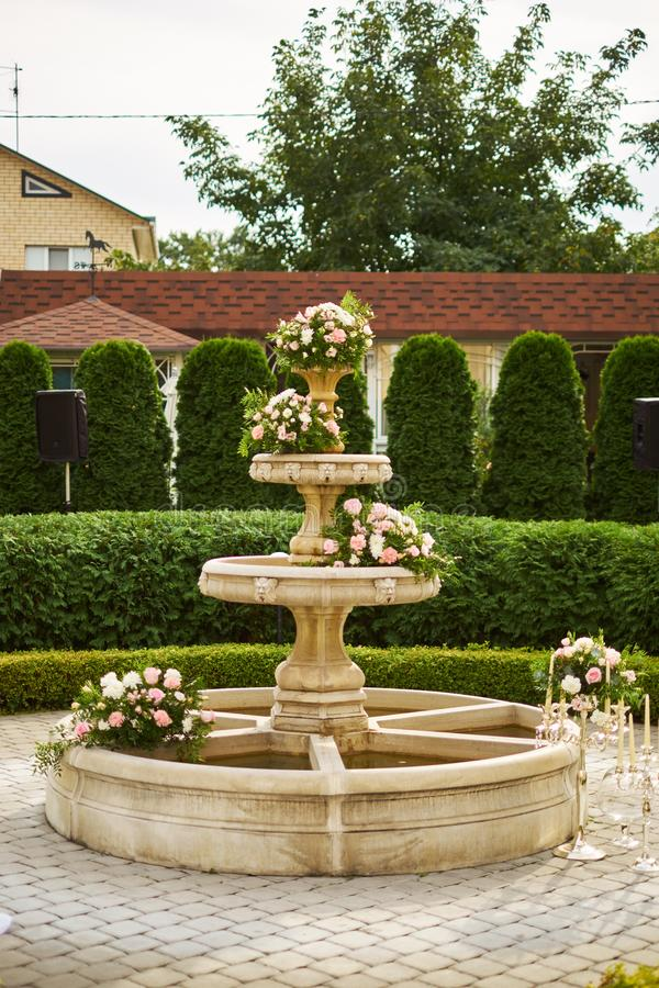 Decoration of a wedding ceremony - flowers in fountain. Wedding decor. Decoration of a wedding ceremony - flowers in the fountain. Wedding decor stock image