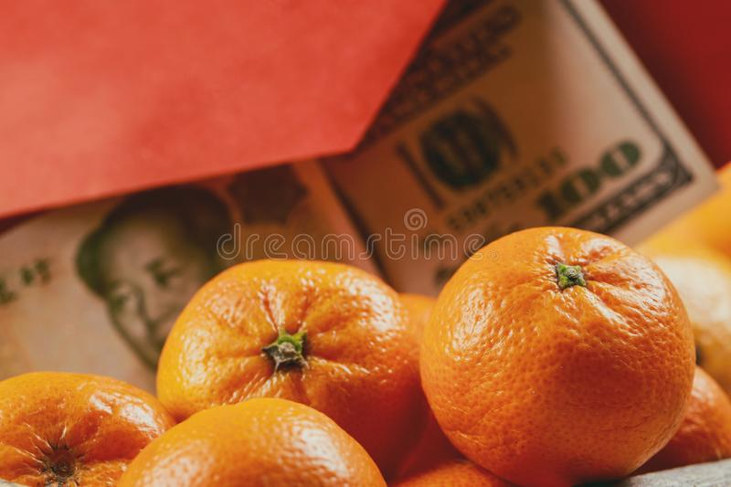 Overhead of top decorations Chinese New Year festive mandarine oranges background concept Chinese Yuan bills vs U.S. dollar stock photo