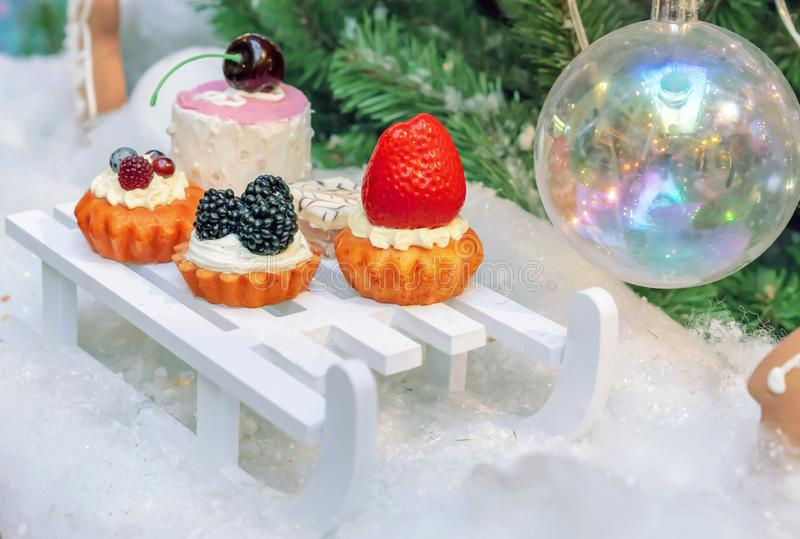 Decorations in the form of a variety of cakes on the background of the Christmas tree stock photography